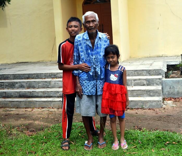 Marsius Marto Sentono (95) bersama dua cucunya di depan Gereja Santa Lidwina, Stasi Suka Bandung, Paroki Santo Yohanes Rasul Kedatong, Sabtu 30 Januari 2016.