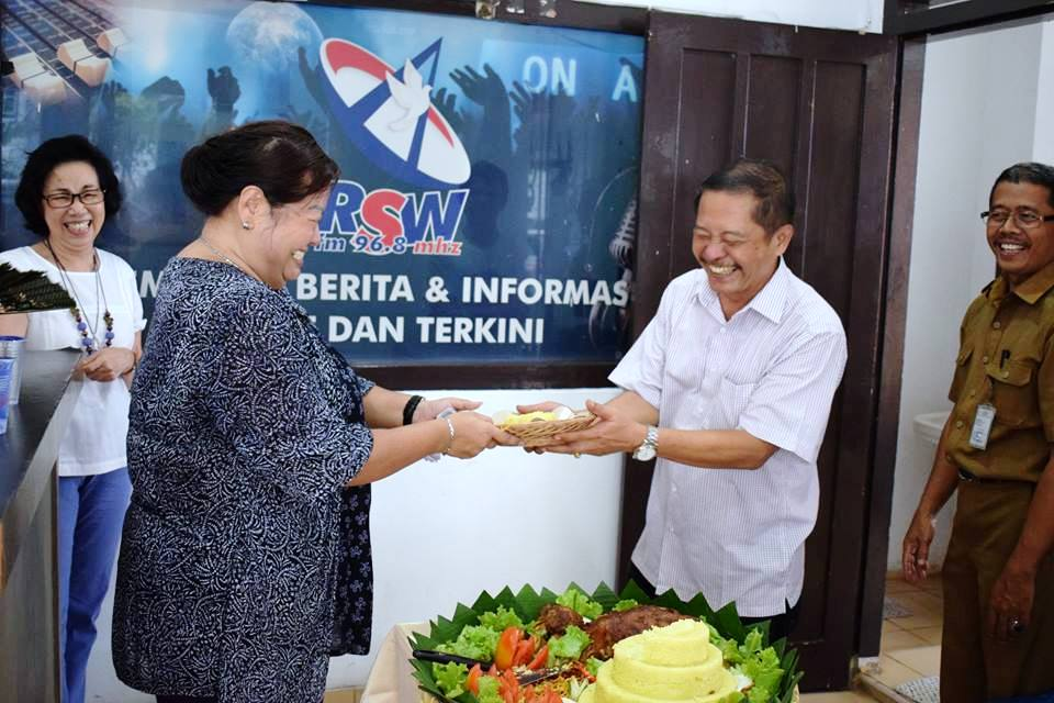 Direktris Radio Suara Wajar Maria Ancilla Cucu Lukman Ali saat memberikan potongan tumpeng pada Ekonom Keuskupan Tanjungkarang RD Yulianus Bambang Condro Saptono.