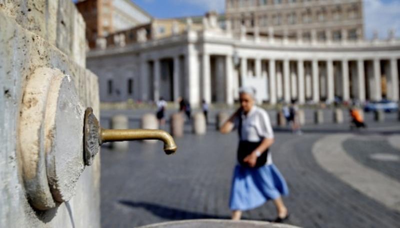 Seorang wanita berjalan di samping sebuah air mancur yang ditutup karena kekeringan di Saint Peter's Square di Vatikan, 25 Juli 2017. | REUTERS/Max Rossi