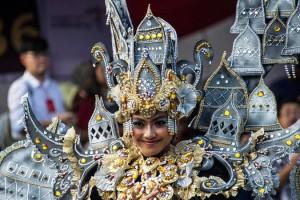 Senyum seorang peserta saat mengenakan kostum adat Indonesia saat berpartisipasi dalam parade Jember Fashion Carnaval 2017 di pulau Jawa timur (13/8). Sekitar 2000 peserta mengelilingi rute 3,6 kilometer di sekitar kota. (AFP Photo/Juni Kriswanto)
