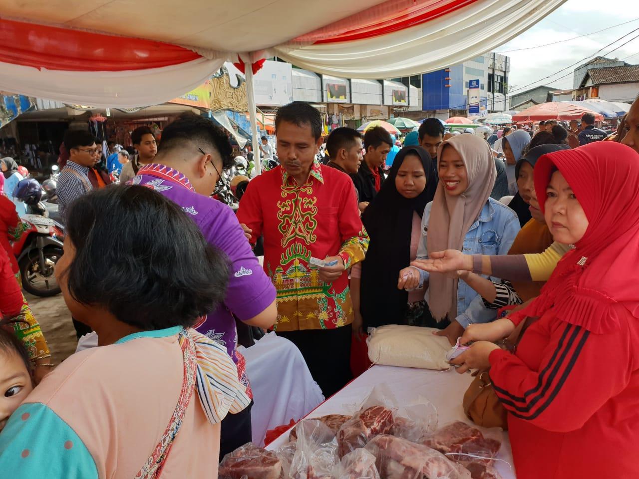 Beberapa pegawai Dinas Ketahanan Pangan Provinsi Lampung terlihat tengah sibuk melayani pengunjung Pasar Murah di Pasar Tugu Bandar Lampung, Minggu, 16 Desember 2018.