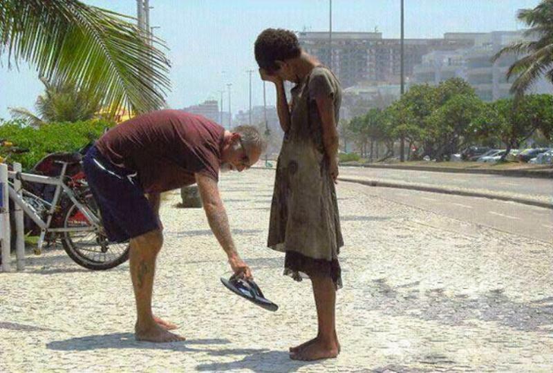 Seorang pria memberikan sepatunya kepada gadis tuna wisma di Rio de Janeiro. (Foto : brilio.net)