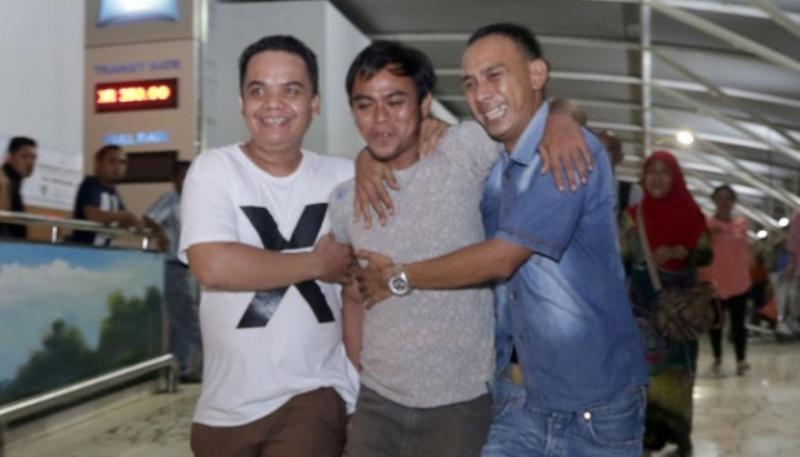 Wawan Saputera (tengah) mantan Sandera milisi Abu Sayyaf dipeluk dua orang kerabatnya saat tiba di bandara Internasional Sultan Hasanuddin, Makassar, Sulawesi Selatan, 3 Mei 2016. Dua warga Makassar yang ikut menjadi korban penyanderaan Abu Sayyaf tiba makassar dan langsung dijemput keluarga. TEMPO/Iqbal lubis