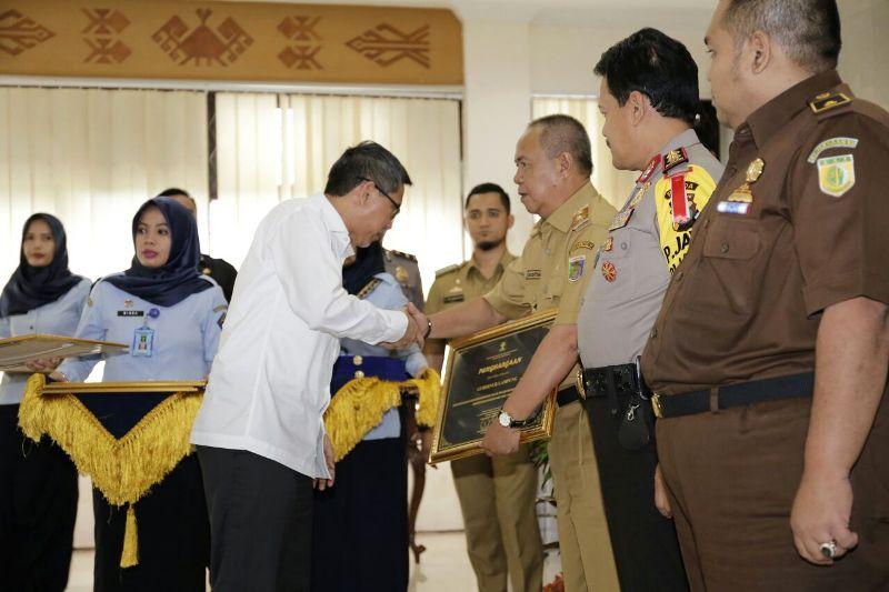 Inspektur Jenderal dari Kementerian Hukum dan HAM RI Haidir Aimin Daud saat menyerahkan penghargaan pada Wakil Gubernur Lampung Bachtiar Basri, Selasa 9 Januari 2018,