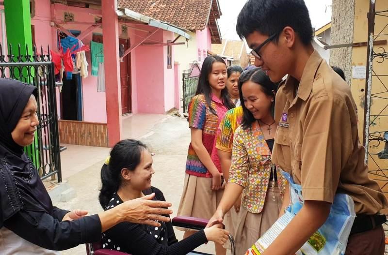 Perwakilan siswa-siswi SMA Xaverius Bandarlampung bersama Dinas Sosial Provinsi Lampung saat menyalurkan bantuan kursi roda kepada penyandang disabilitas di Langkapura Bandarlampung, Kamis, 06 Desember 2019.